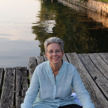 Jasmin Reichel sitzend am Steg auf dem Wasser