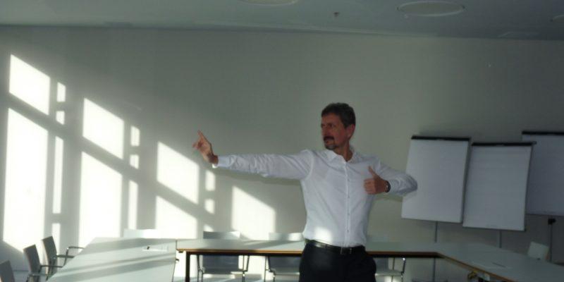 Mann stehend beim Qigong üben in einem Meetingraum