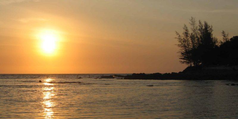Sonnenuntergang am Strand spiegelt sich im Wasser; Meer, Felsen