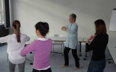 Frauen stehen im Kreis und üben Qigong; in einem Besprechungszimmer, vor einem Fenster